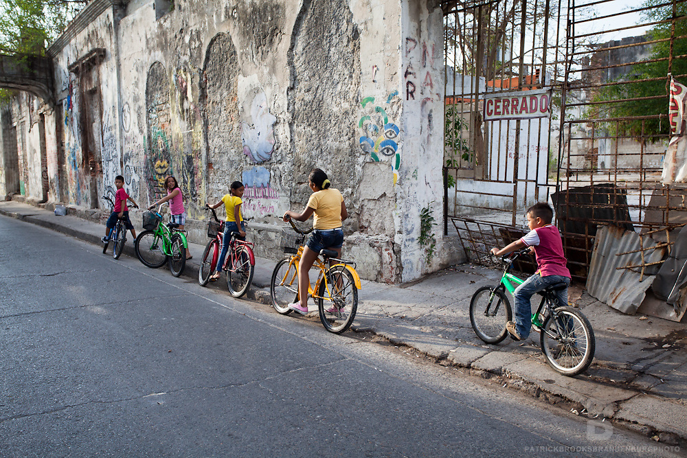 A group of young kids bike through old town Cartagena, Colombia.