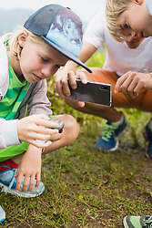 Children with father photographing snail using mobile camera, Mauritius