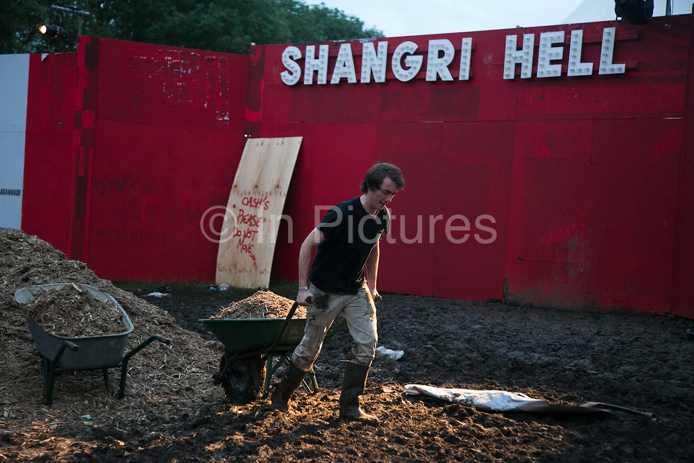 A workers carries saw dust to soak up the mud  at Shangri-la at the Glastonbury Festival 21th July 2016, Somerset, United Kingdom. Shangri-la is a venue at the festival with  art and politics mixed with tunes and all night club nights. Work getting the festival ready takes weeks and in the days up to the festival starts work is frantic.  The Glastonbury Festival runs over 3 days and has 3000 acts, including music, art and performance and approx. 150.000 attend the anual event.