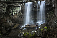 Cradled by an alcove of rocks, Turkey Creek Falls of Hawks Nest State Park, West Virginia, tumbles down the steep cliffside and seemingly disappears beneath a bed of stone that has broken away from the rock wall over time.