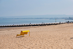 Portobello, Scotland, UK. 25 April 2020. Views of people outdoors on Saturday afternoon on the beach and promenade at Portobello, Edinburgh. Good weather has brought more people outdoors walking and cycling. Police are patrolling in vehicles but not stopping because most people seem to be observing social distancing. Empty beach and s solitary yellow bench. Iain Masterton/Alamy Live News