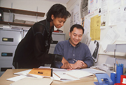 Man and woman at work in office discussing document,