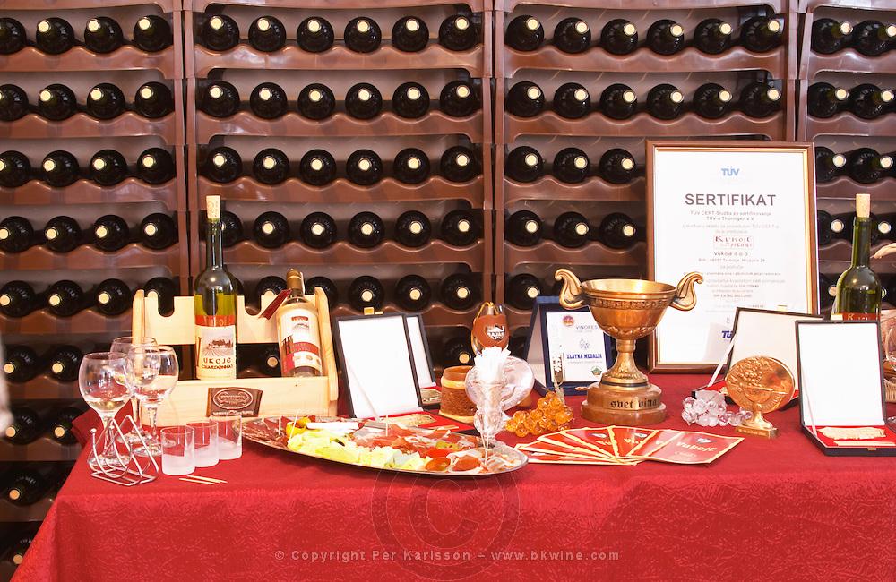 Display with bottles, diplomas glasses promotional material and appetizers., in the winery tasting room. Vukoje winery, Trebinje. Republika Srpska. Bosnia Herzegovina, Europe.
