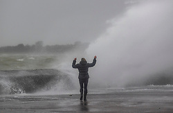 © Licensed to London News Pictures. 09/02/2020. Portsmouth, UK. A woman defies the waves at high tide on the sea front at Southsea, Portsmouth as Storm Ciara batters the UK. Airlines have cancelled dozens of domestic and international flights as the storm brings strong winds and rain. Photo credit: Peter Macdiarmid/LNP