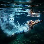 Underwater view of a female diving into clear water in Lake Tahoe, California.
