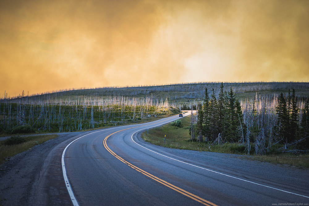Highway 89 twists through a previous burn under orange clouds of smoke from the Reynolds Creek Fire in Glacier National Park as seen from Highway 89. Tuesday, July 21.