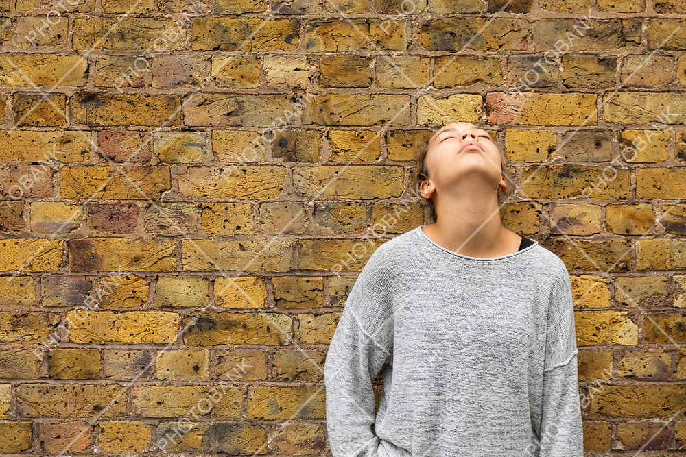 Depressed girl stand in front of a brick wall looking up. Front view.