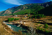 Homes at the foot of mountains in Bhutan. Bridge crossing the river.