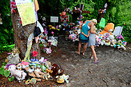 Amanda Williams hugs her daughter Hannah Bain, 7, of Eldridge, Iowa, while visiting the site where the body of two-year-old Caylee Anthony was found on what would have been her sixth birthday in Orlando, Fla., Tuesday, Aug. 9, 2011.  Casey Anthony was acquitted of the most serious charges related to her daughter Caylee Anthony's death.(AP Photo/Phelan M. Ebenhack)