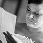 A bride is seen crying after reading a letter from the groom before their ceremony in this black and white photograph. ©Travis Bell Photography