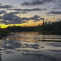 A sunset reflects in Lake of the Woods, Ontario, Canada.