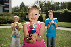 Girl in front of two boys holding trophy