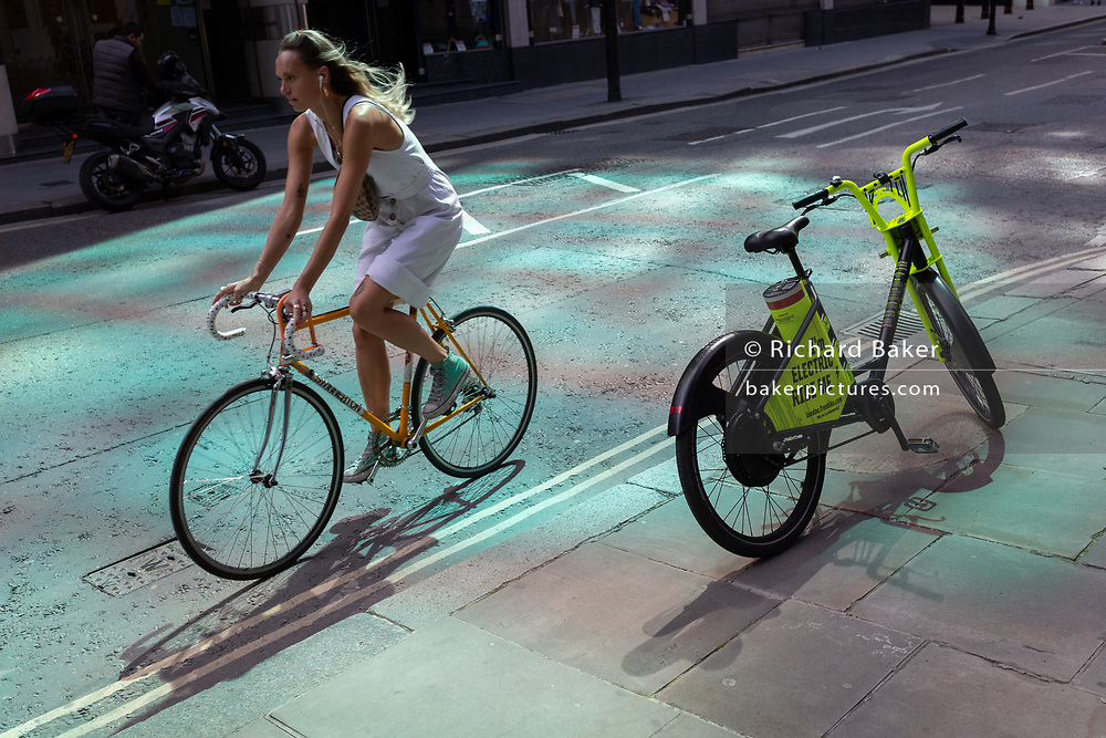 A lady cyclist on her own bicycle pedals past an electric rental Freebike standing on the pavement in reflected light, in the City of London, the capital's financial district, on 20th July 2020, in London, England.