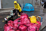 A mother rushes past piled waste in plastic bags awaiting collection by Westminster collection staff in front of a homeless tent on St. Martins Lane, on 15th June 2019, in London, England.