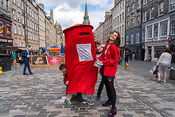 Edinburgh, Scotland, UK. 13th August  2021. Performers from the UCL Graters theatre group promote their Post Office themed show Post Humour on the Royal Mile today.  Iain Masterton/Alamy Live news.