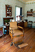 A chair awaits customers at W.D. Moses Barber Shop, built 1879. Barkerville Historic Town & Park, British Columbia, Canada. Historically the main town of the Cariboo Gold Rush, Barkerville is now the largest living-history museum in Western North America. The town was named after Billy Barker from Cambridgeshire, England, who struck gold here in 1861, and his claim became the richest and the most famous. This National Historic Site nestles in the Cariboo Mountains at elevation 1200m (4000ft), at the end of BC Highway 26, 80 kilometres (50 mi) east of Quesnel. Gold here was first discovered at Hills Bar in 1858, followed by other strikes in 1859 and 1860. Wide publication of these discoveries in 1861 began the Cariboo Gold Rush, which reached full swing by 1865 following strikes along Williams Creek.