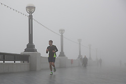 © Licensed to London News Pictures. 13/03/2014. London, UK. People jog and walk on the Thames path near Tower Bridge during thick fog in London this morning, 13th March 2014. Photo credit : Vickie Flores/LNP