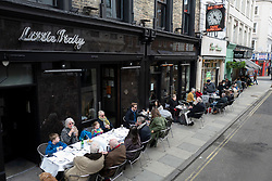 © Licensed to London News Pictures. 12/04/2021. London, UK. Members of the public eat and drink at tables outside Little Italy in Soho in central London. From today restaurants will reopen with outdoor dining following the easing of lockdown restrictions. Photo credit: George Cracknell Wright/LNP