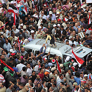A father looks on anxiously as his daughter scales a van surrounded by people during the Day of Justice and Cleansing protest in Cairo's Tahrir Square.