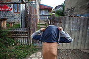 """A boy covering his face with his T-Shirt at the Roma part of the district """"Podsadek"""". The town of Stara Lubovna has a population of 16350, of whom 2 060 (13%) are of Roma origin. The majority of Roma live in the Podsadek district, where 980 (74%) out of 1330 inhabitants are Roma."""