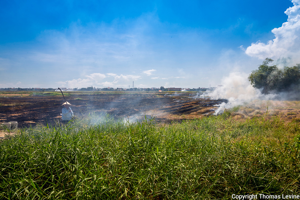 Farmer works his rice field and burns straw from his rice harvest.