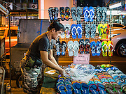 26 MAY 2016 - BANGKOK, THAILAND:  A man who sells shoes and flip-flops in the Silom Road night market sets up her stand before the market opened. The night market on Silom Road, close to Bangkok's famous Patpong tourist area, is being closed by the Bangkok municipal government. Vendors have been told they have to leave the sidewalk on Silom Road by the end of May, 2016. The market is the latest street market being shut down by city officials as a part of the government's plan to clean up Bangkok. The Silom Road night market sells mostly tourist oriented clothes, inexpensive Thai art, and bootleg movies on DVD.      PHOTO BY JACK KURTZ