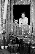 A mother, her son and their dog, pose in their shack in the Movimentodos Trabalhadores Rurais Sem Terra camp, near Iguacu, Brazil. The MST carries out land reform in a country mired by unjust land distribution. In Brazil, a tiny proportion of landowners control roughly half of agricultural land: just 3% of the population owns two-thirds of all arable lands. Since 1985, the MST have occupied unused land where they have established cooperative farms, houses, schools and clinics.