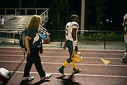 """BIRMINGHAM, AL – SEPTEMBER 11, 2015: Sonya Whitaker (left) and Quintarius Monroe (center) walk to the buses following a game. As a type 1 diabetic, Quintarius Monroe requires frequent blood sugar testing and supervision when self-administering insulin. When care from qualified personnel at his school in Center Point became unavailable, Monroe was forced to transfer several miles away from his locally zoned school to attend Woodlawn High School. The Americans with Disabilities Act requires schools to provide """"reasonable accommodation"""" for students with medical conditions, but given that most schools no longer retain school nurses, many schools are failing to provide adequate care for their students.<br /> CREDIT: Bob Miller for The New York Times"""