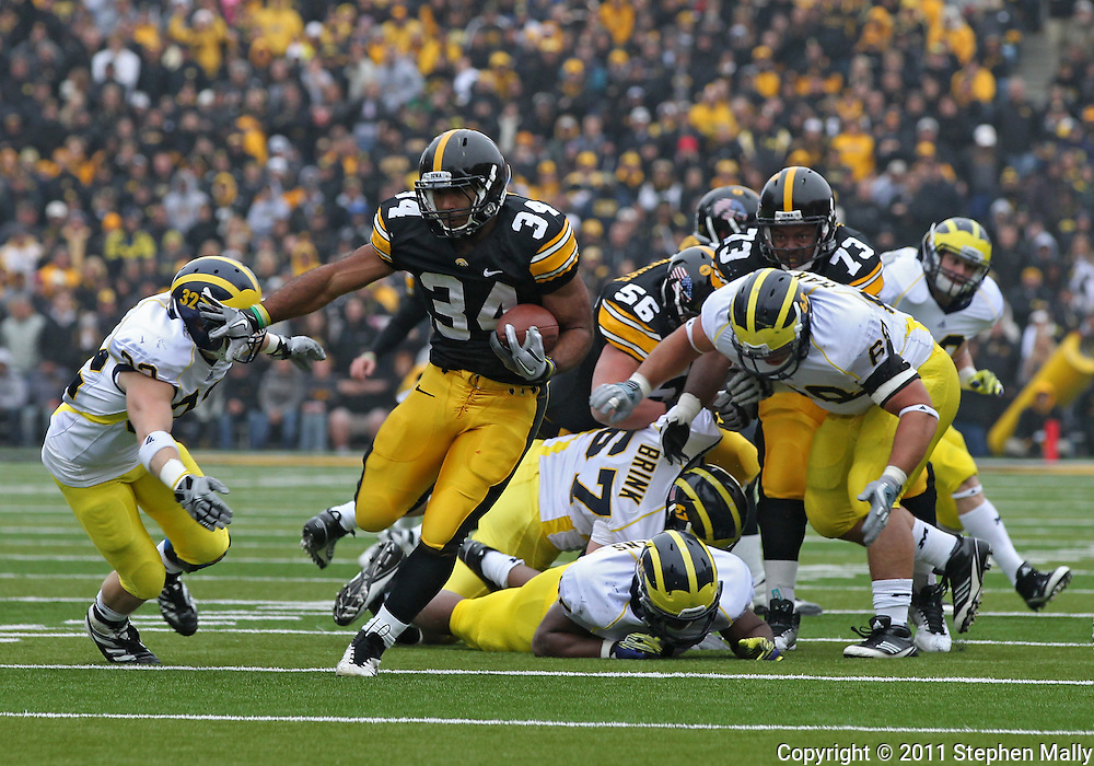 November 05, 2011: Iowa Hawkeyes running back Marcus Coker (34) tries to avoid Michigan Wolverines safety Jordan Kovacs (32) on a run during the second quarter of the NCAA football game between the Michigan Wolverines and the Iowa Hawkeyes at Kinnick Stadium in Iowa City, Iowa on Saturday, November 5, 2011. Iowa defeated Michigan 24-16.