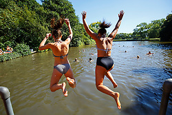 © Licensed to London News Pictures. 23/08/2016. London, UK. People swim in Hampstead Heath Mixed Bathing Pond in north London as they enjoy August's last heatwave on Tuesday, 23 August 2016. Photo credit: Tolga Akmen/LNP