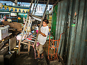 04 JANUARY 2016 - BANGKOK, THAILAND:         A worker removes the frame of shelving in Bang Chak Market after the market closed permanently. The market closed January 4, 2016. The Bang Chak Market serves the community around Sois 91-97 on Sukhumvit Road in the Bangkok suburbs. About half of the market has been torn down. Bangkok city authorities put up notices in late November that the market would be closed by January 1, 2016 and redevelopment would start shortly after that. Market vendors said condominiums are being built on the land.     PHOTO BY JACK KURTZ