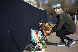 © Licensed to London News Pictures.11/04/2021. London, UK. A woman places flowers outside Buckingham Palace. On Friday the 9th of April Buckingham Palace announced that Prince Philip The Duke of Edinburgh passed away in the morning at Windsor Castle . Photo credit: George Cracknell Wright/LNP