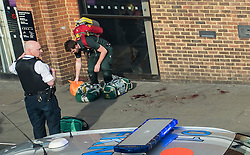 © Licensed to London News Pictures. 05/05/2016. London, UK. A paramedic (left) stands next to a large pool of blood after a stabbing outside the McDonalds in Camberwell, South London. According to reports on Twitter, a large knife fight broke out between groups of school children with multiple stabbings. Photo credit: Rob Pinney/LNP