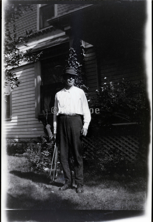 adult man standing in front of house 1920s USA