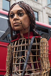 London, UK. 23rd October, 2021. Little Amal, a giant puppet of a Syrian refugee girl fleeing conflict, approaches St Paul's Cathedral. The 3.5-metre puppet, which is nearing the end of an 8,000km journey from the Turkish-Syrian border to Manchester in support of refugees, climbed the steps of St Paul's Cathedral to present a wood carving of a ship at sea from St Paul's birthplace at Tarsus in Turkey to the dean.
