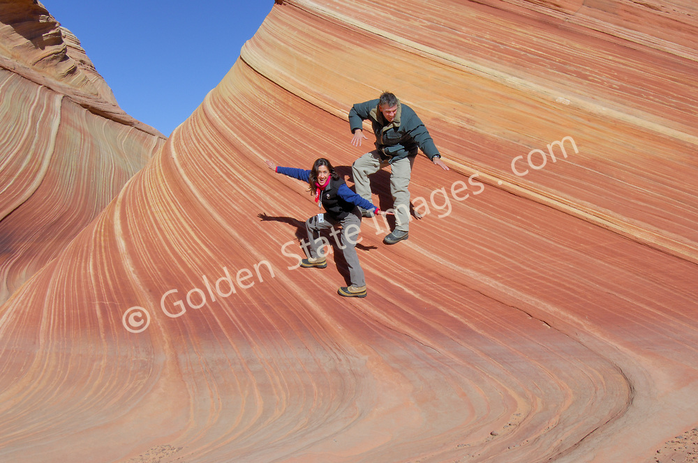 """Surfin' the Wave in Paria Canyon - Vermillion Cliffs Wilderness area in Southern Utah.<br /> <br /> Coyote Buttes North located in the Paria Canyon - Vermilion Cliffs Wilderness. This area features one of the most well-known geologic sandstone formations in the world, called """"The Wave"""".<br /> <br /> The Wave is a spectacular area of sandstone formations twisted into the shapes of breaking waves pillars cones and mushrooms.<br /> <br /> An ancient sea laid down layers of sediment deposits which hardened to form the multicolored sandstone rock. Over eons the actions of water the cycles of baking heat and subfreezing temperatures and wind have formed its complex undulating shapes.<br /> <br /> The deep reds of the rock and their shapes appear to change with the seasons and time of day."""
