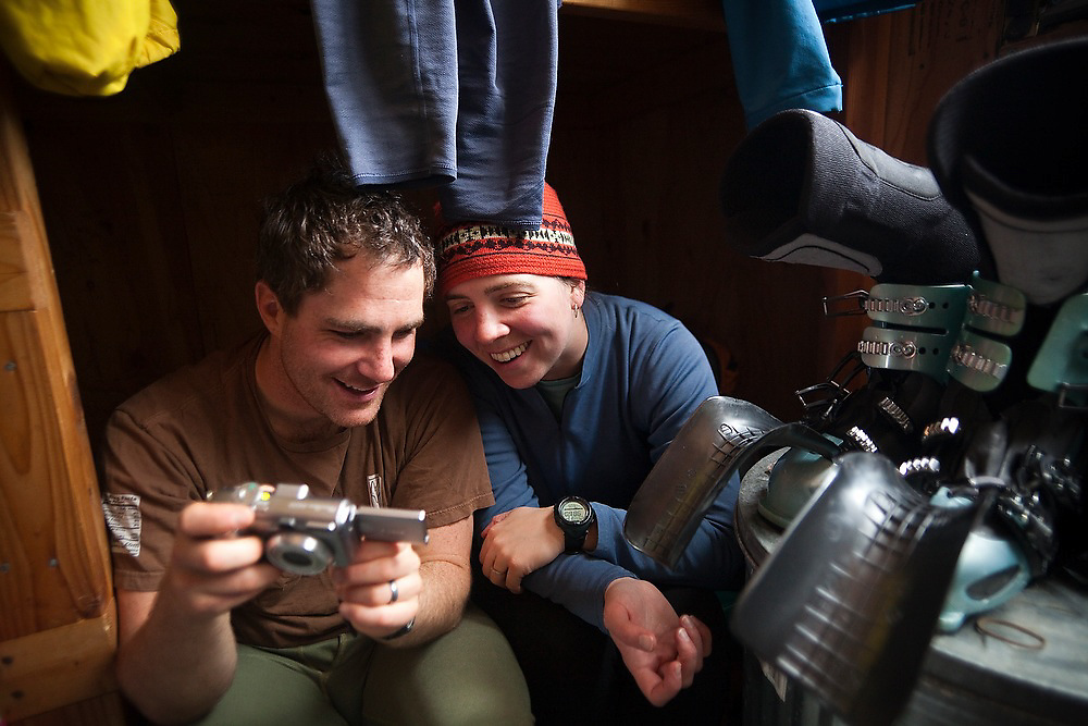 Judd MacRae and Emily Miller sit in their bunk surrounded by drying ski gear looking at the day's photos, North Pole Hut, San Juan Mountains, Colorado.