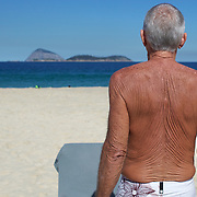 A man with sunbaked skin on the beach at Ipanema, Rio de Janeiro,  Brazil. 6th July 2010. Photo Tim Clayton..
