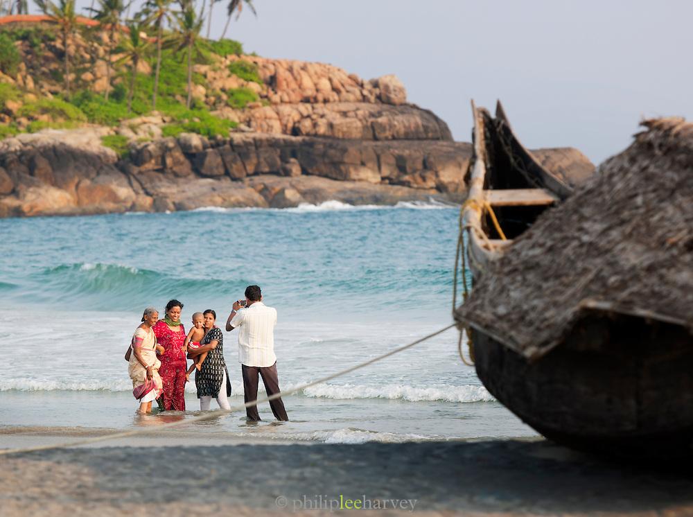 A family take photographs on Kovalam Beach, near Trivandrum (Thiruvananthapuram), Kerala, India