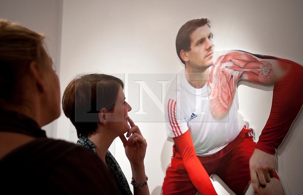 © Licensed to London News Pictures. 12/03/2012. London, UK. Jo Culley (left) and a gallery visitor admire her illustration of hockey player Richard Smith's shoulder muscles. Photo credit : Spike Johnson/LNP