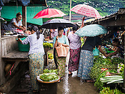 14 JUNE 2013 -  PANTANAW, AYEYARWADY, MYANMAR: Shoppers under umbrellas during a rain storm in the market in Pantanaw, in the Ayeyarwady Region of south-west Myanmar. It is the hometown of former United Nations Secretary-General U Thant and of the renowned artist U Ba Nyan.   PHOTO BY JACK KURTZ