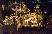 A man sits by the candlelit gravesite of a family member during the Day of the Dead festival October 31, 2017 in Tzintzuntzan, Michoacan, Mexico.