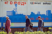 Perm, Russia, 01/06/2006..Crude advertising slogans for local businesses painted on the perimeter walls of a city centre construction site.