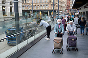 Elderly women wearing face masks pass up the ramp near construction site for work on the update to the Midland Metro tram public transport system in the city centre along Corporation Street on 3rd August 2021 in Birmingham, United Kingdom. The original tracks are being pulled up and relaid, while a new line is also under construction and due to open later in the year. The Midland Metro is a light-rail tram line in the county of West Midlands, England, operating between the cities of Birmingham and Wolverhampton via the towns of West Bromwich and Wednesbury. The line operates on streets in urban areas, and reopened conventional rail tracks that link the towns and cities. The owners are Transport for West Midlands with operation by National Express Midland Metro, a subsidiary of National Express. TfWM itself will operate the service from October 2018.