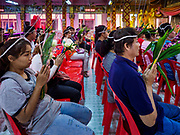 """30 DECEMBER 2017 - BANG KRUAI, NONTHABURI, THAILAND:  People pray during a resurrection ceremony at Wat Ta Khien, about 45 minutes from Bangkok in Nonthaburi province. The temple is famous for the """"floating market"""" on the canal that runs past the temple and for the """"resurrection ceremonies"""" conducted by monks at the temple. After the prayer, they lie in a coffin and ritualistically die before being reborn. Adherents believe it will improve their karma and help make up for past sins. PHOTO BY JACK KURTZ"""