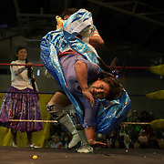 Carman Rosa is thrown by her male counterpart as her tag team mate Yolanda La Amorosa looks on during the 'Titans of the Ring' wrestling group's Sunday performance at El Alto's Multifunctional Centre. Bolivia. The wrestling group includes the fighting Cholitas, a group of Indigenous Female Lucha Libra wrestlers who fight the men as well as each other for just a few dollars appearance money. El Alto, Bolivia, 11th April 2010. Photo Tim Clayton