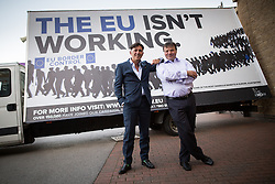 """© Licensed to London News Pictures . 25/09/2015 . Doncaster , UK . ANDY WIGMORE and AARON BANKS in front of an ad trailer with """" The EU isn't working """" at the 2015 UKIP Party Conference at Doncaster Racecourse , this morning (Friday 25th September 2015) . Photo credit : Joel Goodman/LNP"""