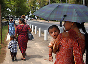 A Hindustani woman walks with her child along the Waterkant district in Paramaribo, Suriname, Saturday, September 27, 2003. (Photographer: Emile Wamsteker)