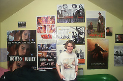 Teenage girl standing in bedroom with posters on wall in background,
