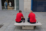 During the UKs Coronavirus pandemic lockdown and in the 24hrs when a further 255 deaths occurred, bringing the official covid deaths to 37,048, <br /> two workmen in matching shirts sit and talk close to each other on an empty Oxford Street, on 26th May 2020, in London, England.